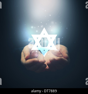 Female hands opening to light and David's star. Jewish religion - Stock Photo
