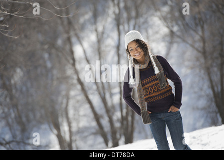 Winter scenery with snow on the ground. A young woman wearing a woolly hat. - Stock Photo