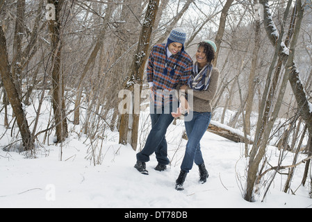 Winter scenery with snow on the ground. A couple arm in arm walking through the woods. - Stock Photo