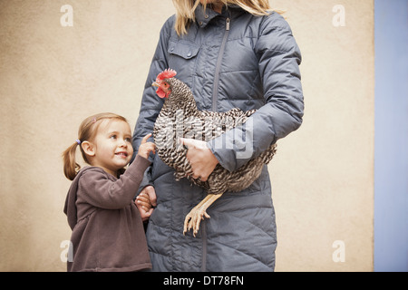A woman in a grey coat holding chicken with a red coxcomb under one arm. A young girl beside her holding her other - Stock Photo