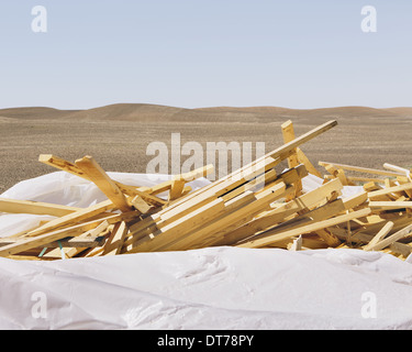 White tarp covering pile of wood 2x4 studs, farmland in background, near Pullman - Stock Photo