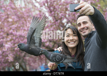 A couple, a man and woman, in the park, taking a selfy, self portrait with a mobile phone. Two pigeons perched on - Stock Photo