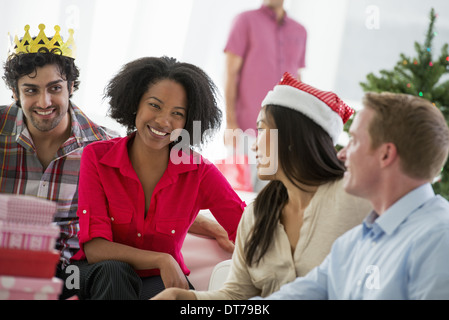 A woman wearing a red and white Father Christmas hat at a party, with friends, Five laughing decorated Christmas - Stock Photo