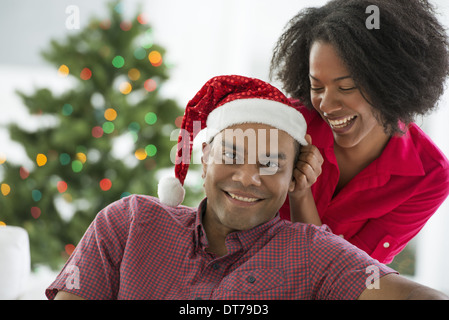 A man in a Father Christmas hat. At home. A decorated Christmas tree. - Stock Photo