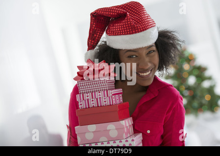 A woman wearing a red and white Father Christmas hat.  At home. A decorated Christmas tree. - Stock Photo