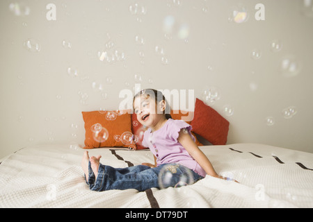 A young girl with brown eyes and dark hair in bunches sitting on a bed laughing. Bubbles floating in the air. - Stock Photo