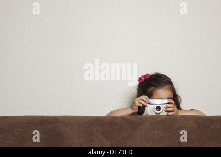 A young three year old girl crouching behind a sofa, with a toy camera, taking a picture. - Stock Photo