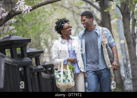 A couple walking in the park side by side carrying shopping bags. - Stock Photo