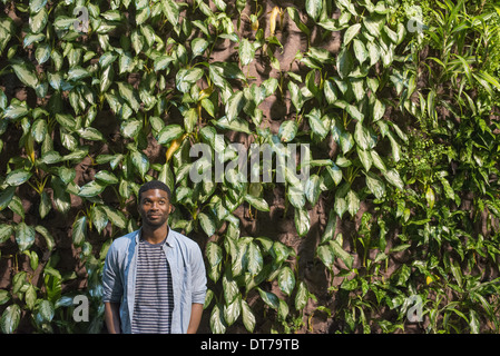 A man standing in front of a wall covered in climbing plants and ivy. - Stock Photo