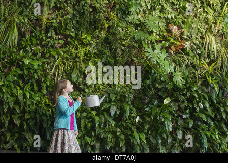 A young girl standing in front of a wall covered with ferns and climbing plants. - Stock Photo