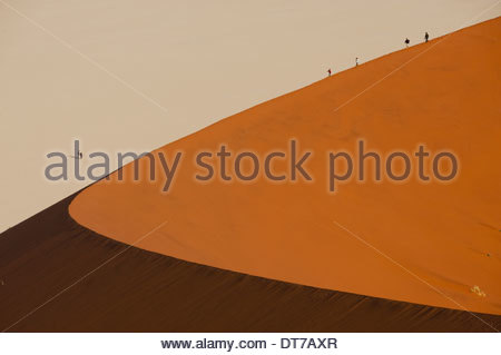 Hikers climbing up a sand dune ridge at Sossusvlei Namib-Naukluft National Park Namibia landscape wilderness - Stock Photo