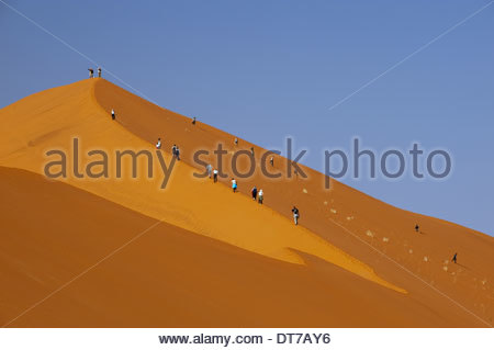 Hikers climbing up a sand dune ridge at Sossusvlei Namib-Naukluft National Park Namibia natural world landscape - Stock Photo