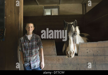 A man standing by horsebox in the stables at an animal sanctuary A horse with its head over the gate Saugerties - Stock Photo