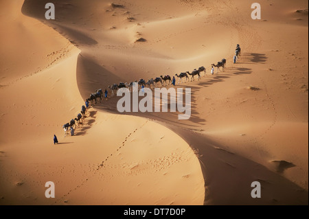 setting sun over desert shadow as a caravan camel merchants winds their way toward the next stop on their journey - Stock Photo
