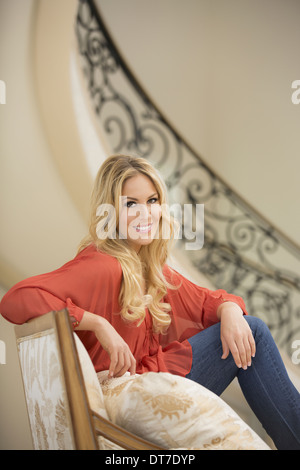 A woman with blonde hair sitting in an armchair with thick cushions in the hallway of an elegant mansion Lago Vista - Stock Photo