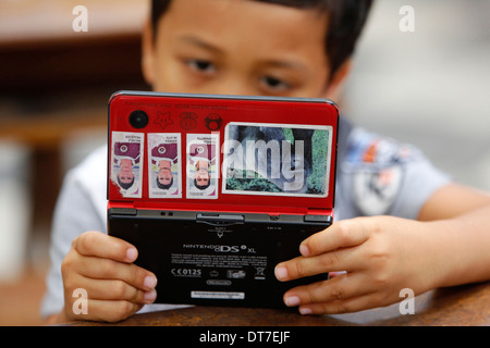 Boy playing with a games console - Stock Photo