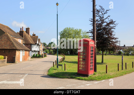 Traditional old red telephone box and telegraph pole on a village green in Stour Valley. Chartham, Kent, England, - Stock Photo