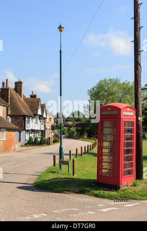Traditional old red telephone box and telegraph pole on a village green in Chartham, Kent, England, UK, Britain - Stock Photo