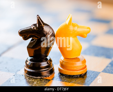 Chess black and white knights standing on old vintage chessboard - Stock Photo