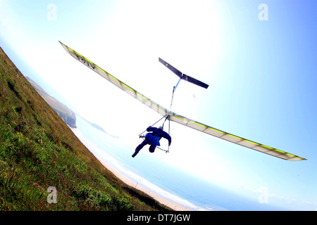 man taking off on hang glider at Rhossili on the Gower Peninsular, Wales, UK - Stock Photo