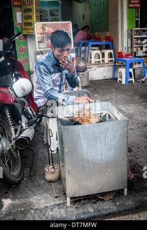 HANOI, VIETNAM, JANUARY 27: Vietnamese man cooking on the street. A common sight in the countries capital city Hanoi. - Stock Photo