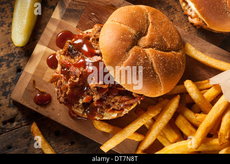 Barbeque Pulled Pork Sandwich with BBQ Sauce and Fries - Stock Photo