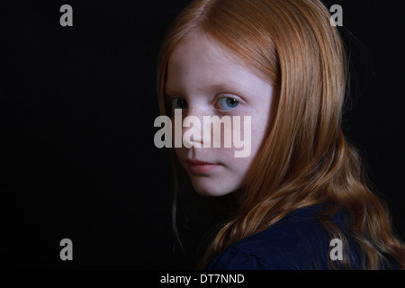 A freckled red haired little girl looks sadly over her shoulder in to camera. Isolated on black landscape - Stock Photo