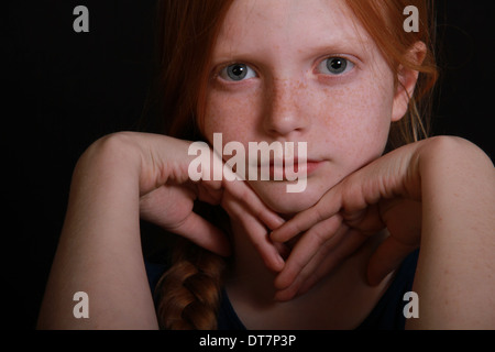 Angry little girl stares into camera on a black background her head is rested on her hands - Stock Photo