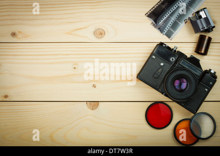 Old retro camera and film roll on wooden boards. Focus on camera. Abstract background - Stock Photo