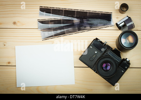 Old retro camera and film roll on wooden boards. - Stock Photo