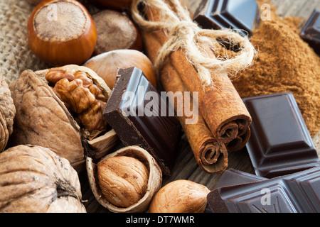 Ripe hazelnuts, walnuts, cinnamon sticks and chocolate - Stock Photo