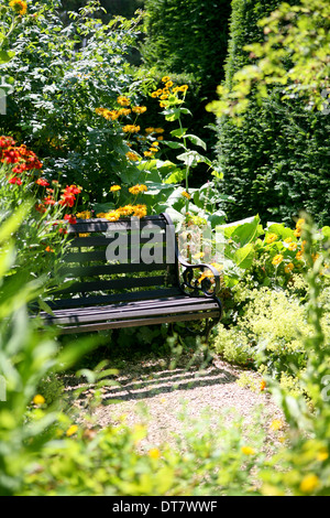 Secluded garden bench surrounded by planting - Stock Photo