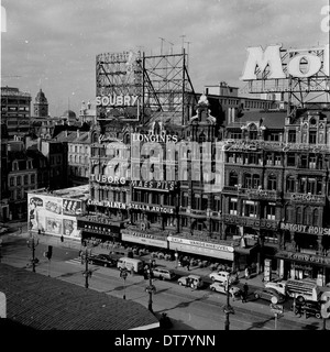Historical picture from 1950s showing a street in Brussels, Belgium with buildings with advertising hoardings or - Stock Photo