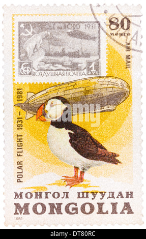 Stamp printed in Mongolia shows the image of the Graf Zeppelin & Puffin from the series 'Polar Flight - Stock Photo