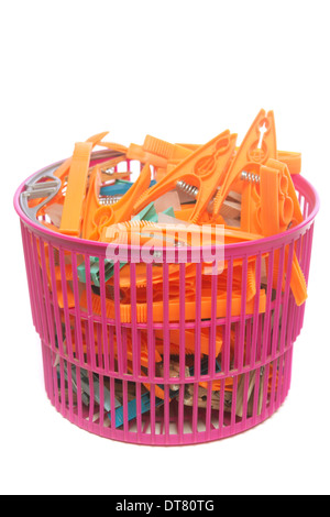 Colored clothes pegs in plastic basket isolated over white background - Stock Photo