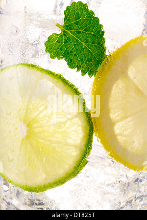 A close up detail of a lemon lime soda with a mint leaf with ice in a clear glass - Stock Photo