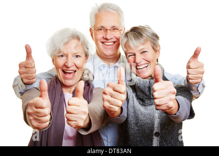 Three happy senior people holding their thumbs up - Stock Photo