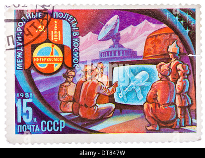 stamp printed in USSR shows Intercosmos program - the people of Mongolia are watching on television flight Space - Stock Photo