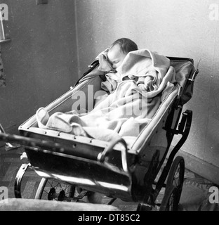 Historical picture from 1950s showing a sleeping baby in her pram. - Stock Photo