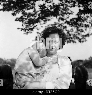Historical picture from 1950s showing a mother with a sleeping baby on her shoulder, - Stock Photo
