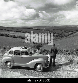 Historical picture from 1950s showing a man standing next to his parked car admiring the view of the countryside - Stock Photo