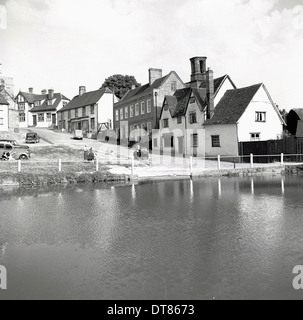Historical picture from 1950s showing a row of cottages on a hill above a village pond, England. - Stock Photo