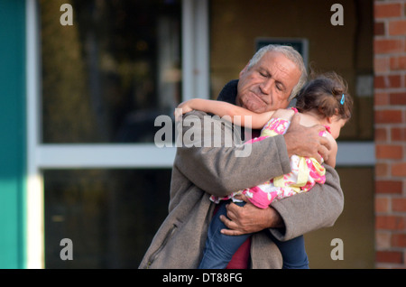 Grandfather embrace his granddaughter after family disaster. - Stock Photo