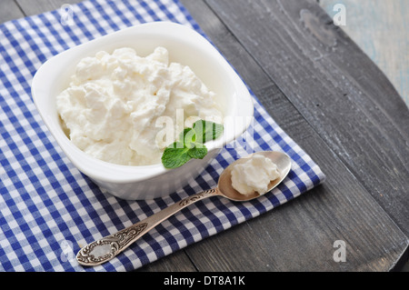 Ricotta cheese in bowl with mint on wooden background - Stock Photo