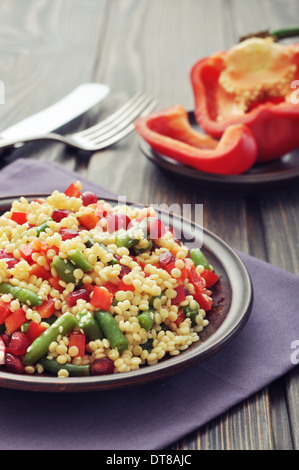 Salad with couscous, sweet pepper, green bean, pomegranate and sesame on plate closeup - Stock Photo