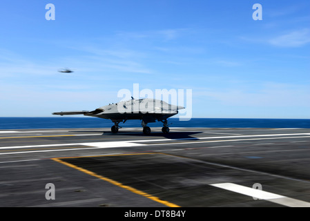 An X-47B unmanned combat air system conducts a touch and go landing. - Stock Photo