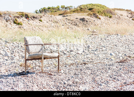 Old worn out chair outside on a land covered with small stones - Stock Photo