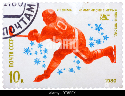 stamp printed in USSR,13 Olympic Winter Games, Lake Placid, United States, Hockey, hockey player bats the puck - Stock Photo