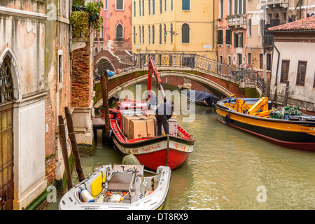 Venice, Italy. Freight-laden barge with mounted crane in a narrow Venetian canal unloading containers. - Stock Photo
