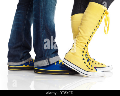 Closeup of woman and man legs in colorful blue and yellow trainers shoes isolated on white background - Stock Photo
